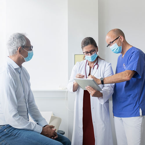 Patient, doctor and nurse wearing facemasks, in a clinic, discussing test results