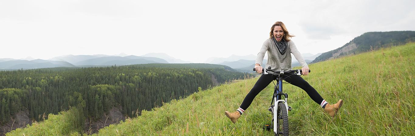 Female mountain biker, rolling down a hill