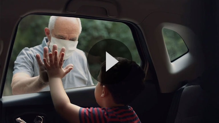 Elderly man wearing face mask standing outside car, touching palm of hand on window glass with child inside car