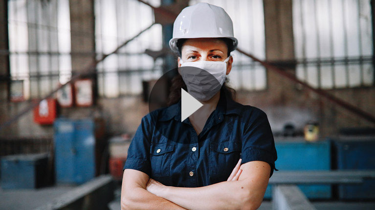 Female manufacturing worker wearing work clothes, hard hat and face mask, in a small factory setting.