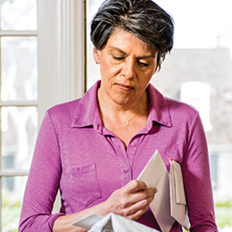 Lady in living room, reviewing her mail
