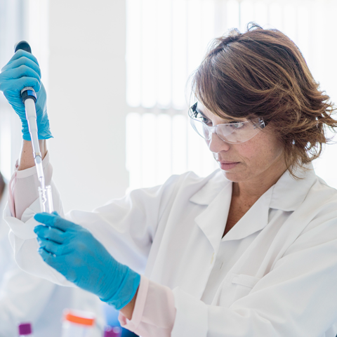 Female lab scientist filling a vial with a liquid sample