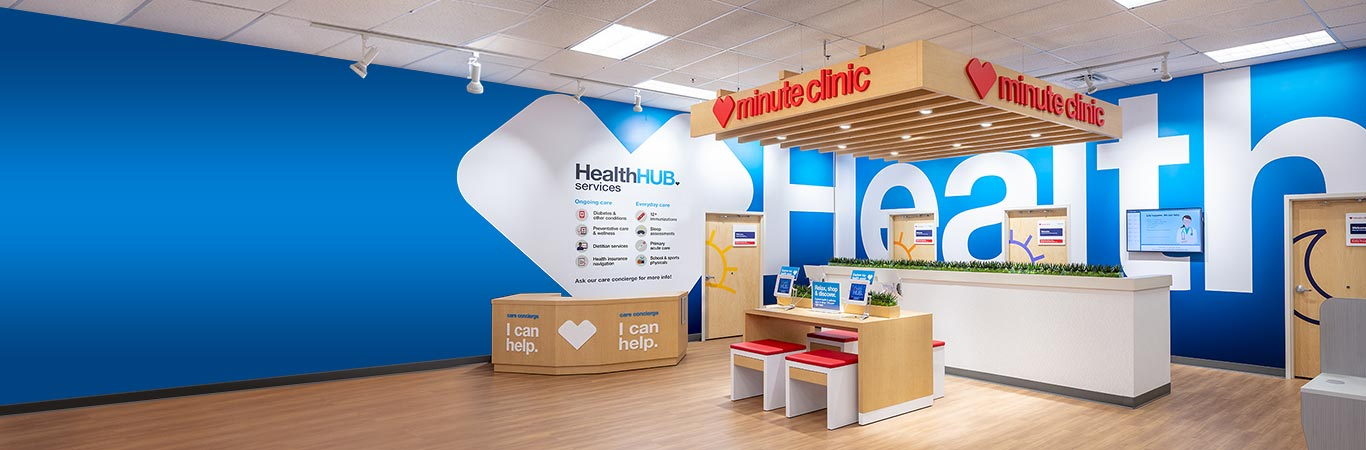 Photo of a HealthHUB Concept Store, with MinuteClinic signs, central service counter, and consultation rooms along one wall