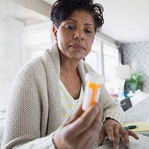 Female patient reading the information on a prescription pill bottle