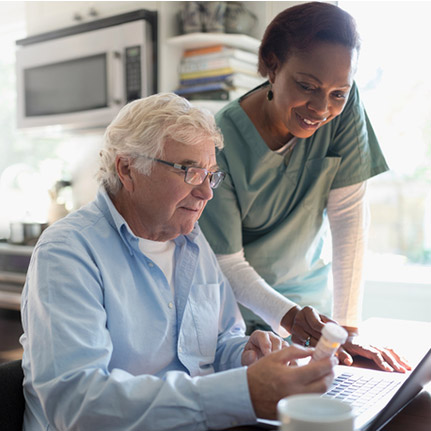 Nurse and patient viewing prescription information on a laptop computer