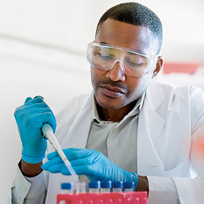 Male scientist filling liquid drug samples into vials