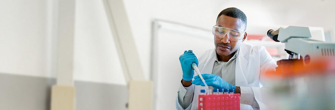 Male scientist filling liquid drug samples into vials