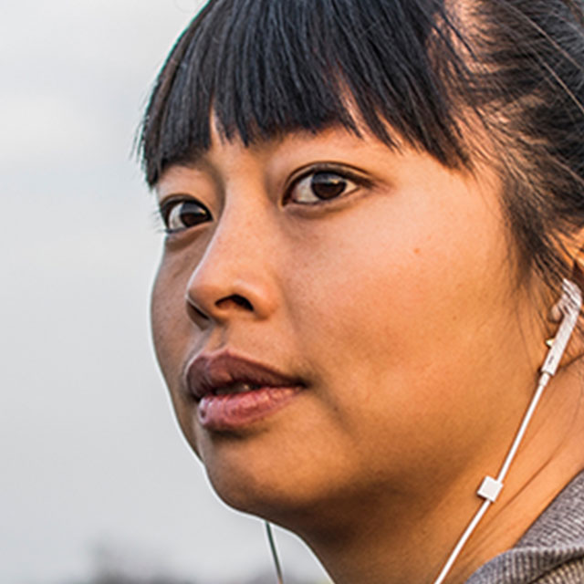 Young woman walking outdoors with headphones