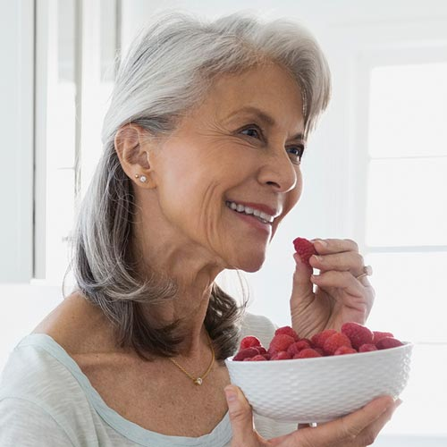 Elderly lady eating cherries