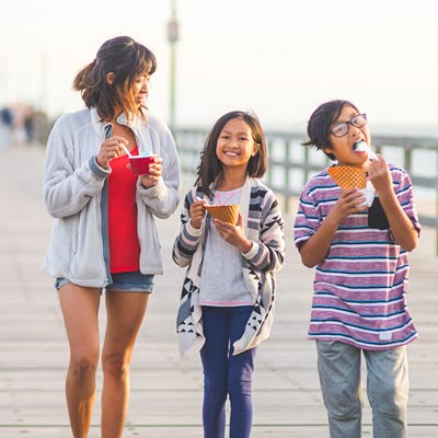 Three teenagers eating ice cream on a pier
