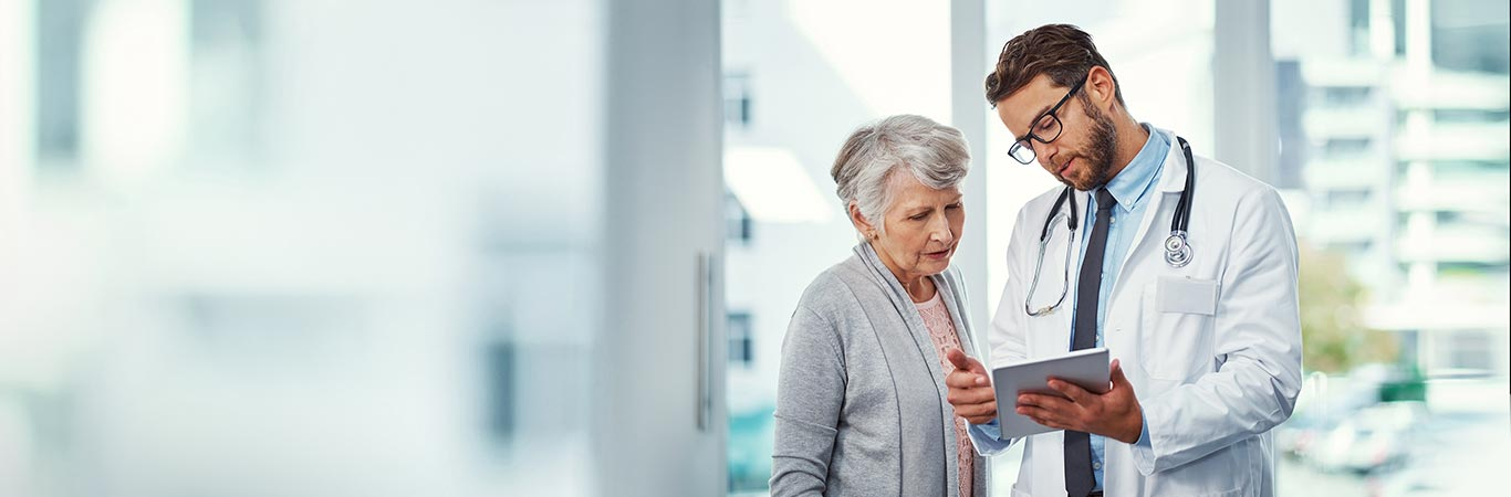 Male doctor and elderly lady reviewing medical information