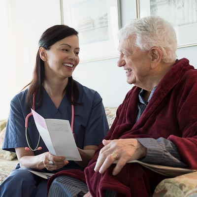 Female caregiver and elderly patient discussing medical information on a couch