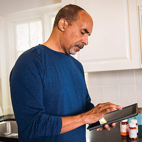 Man using a tablet device in his kitchen