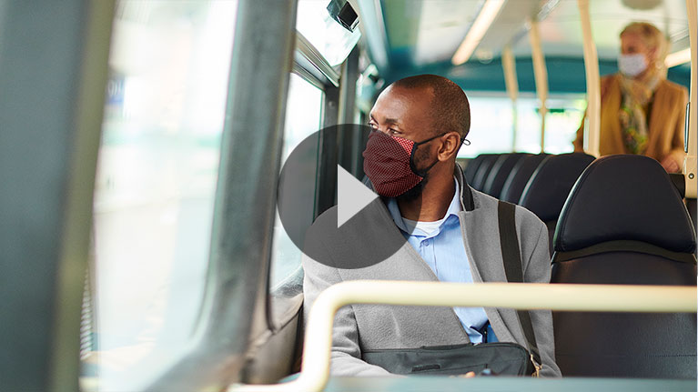 African american office worker, in the bus, wearing facemask, on the way to work