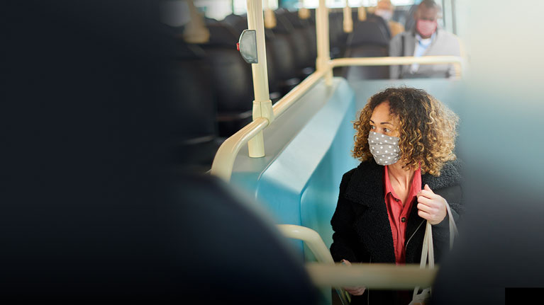 Female office employee in a train station, on her way to work, wearing a face mask.