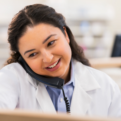 A smiling pharmacist talks on the phone