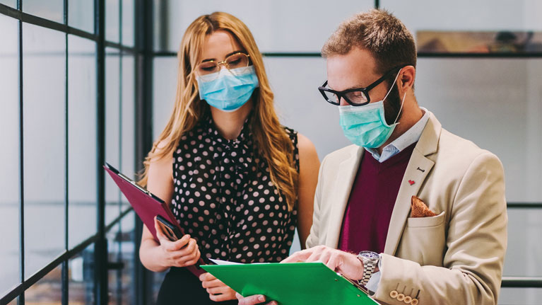 Two workers in an office building, wearing facemasks, discussing data